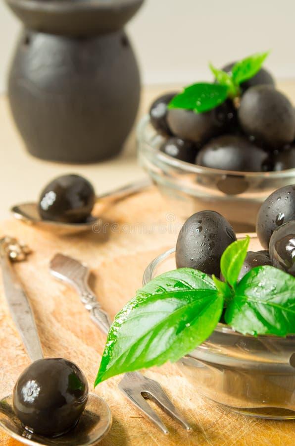 Czarne oliwki zakrywać w oleju z zielonymi liśćmi obrazy royalty free