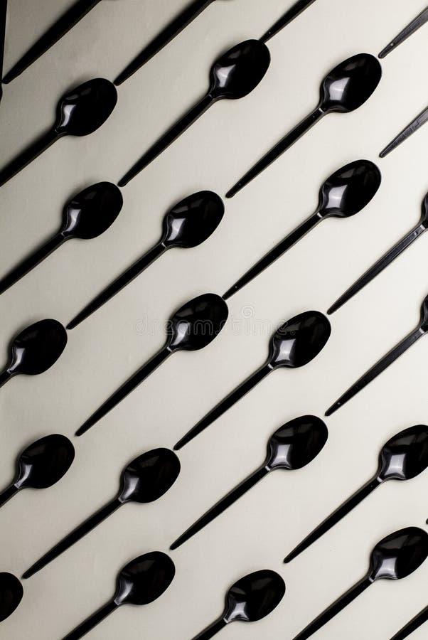 Czarne plastikowe łyżki na szarym tle fotografia stock