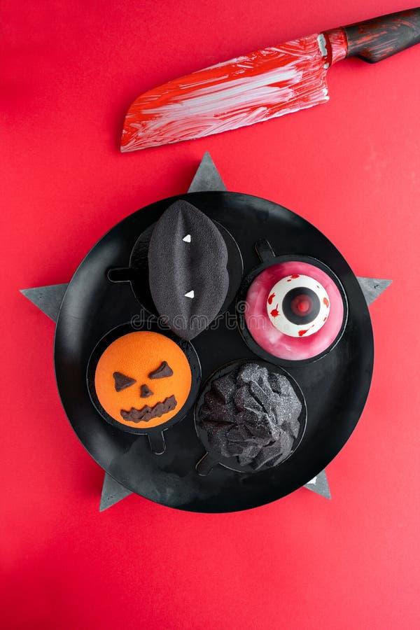 Czarne wargi z wampirów fangs, poszarpanym okiem, złowieszczą banią i czarną górą, Halloweenowy straszny mousse tort z obrazy royalty free