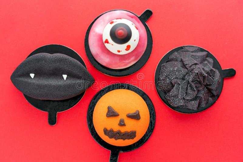 Czarne wargi z wampirów fangs, poszarpanym okiem, złowieszczą banią i czarną górą, Halloweenowy straszny mousse tort z zdjęcia royalty free