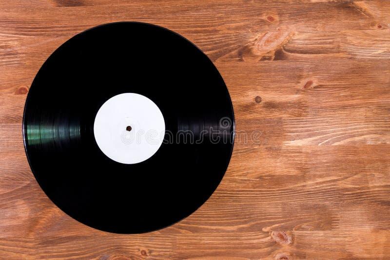 Czarnego koloru winylowy rejestr na brown drewnianym tle zdjęcia royalty free