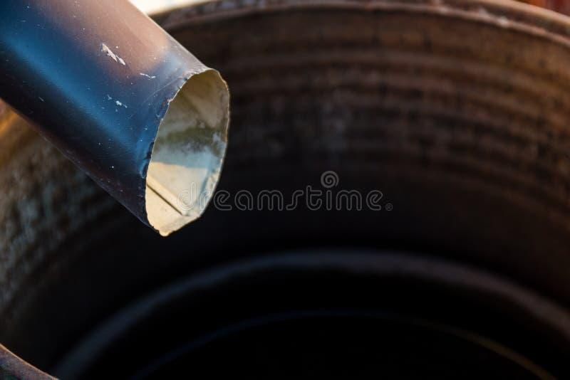 Czarnego metalu rynnowy downspout drenuje w podeszczową baryłkę na pogodnym obrazy stock