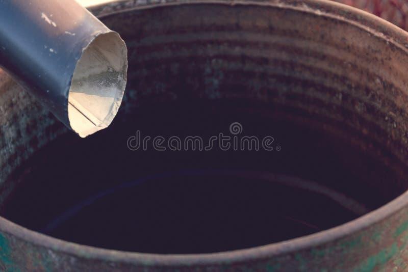 Czarnego metalu rynnowy downspout drenuje w podeszczową baryłkę na pogodnym fotografia stock