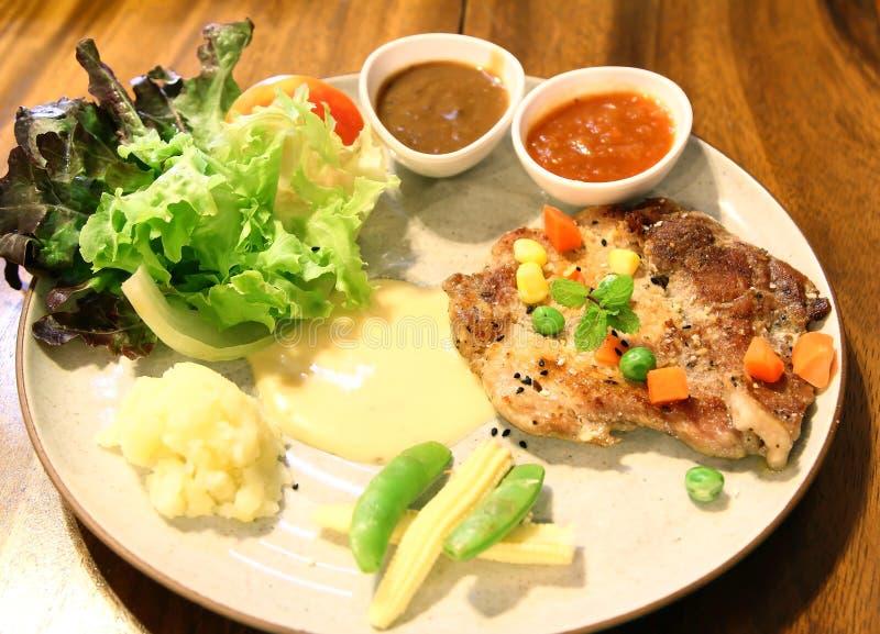Czarnego pieprzu wieprzowiny stek i warzywo sałatka obrazy royalty free