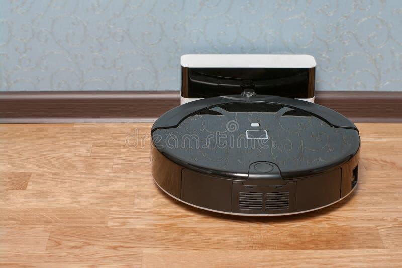 czarnego robota próżniowy czysty na ładuje doku po tym jak ono kończy Nowożytna mądrze elektroniczna housekeeping technologia obraz stock