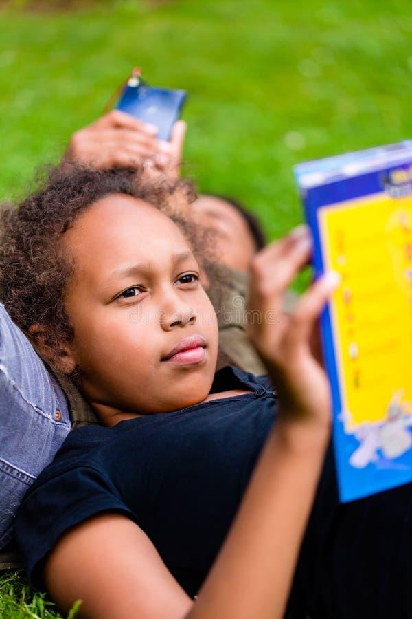 Czarnej dziewczyny czytelnicza książka na łące zdjęcie stock