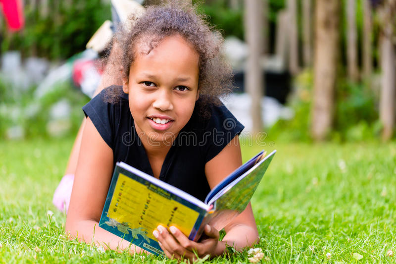 Czarnej dziewczyny czytelnicza książka na łące zdjęcia royalty free