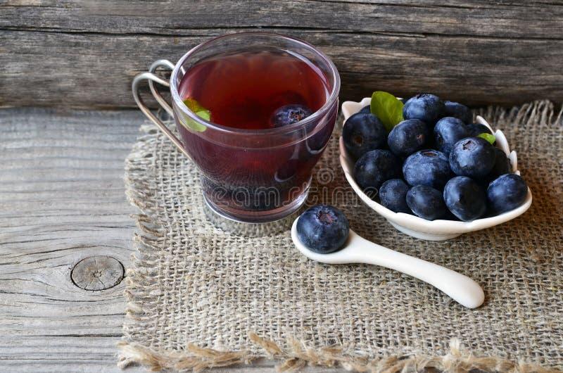 Czarnej jagody herbata w szklanej filiżance świeżych czarnych jagodach na burlap płótnie na drewnianym tle i Naturalny ziołowy na obraz stock