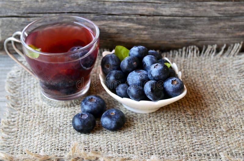 Czarnej jagody herbata w szklanej filiżance świeżych czarnych jagodach na burlap płótnie na drewnianym tle i Naturalny ziołowy na obrazy royalty free