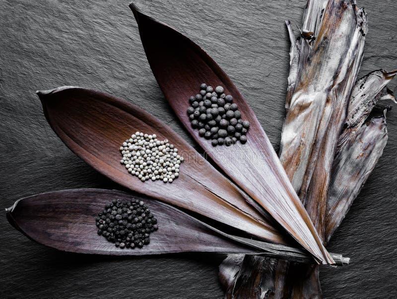 Czarni, Biali i Fragrant stosy pieprze w Suchym liściu, Leją o obrazy stock