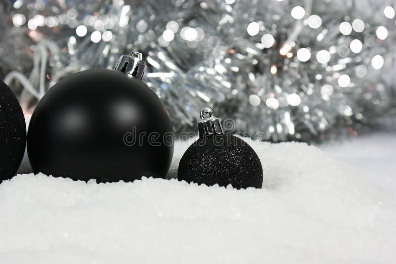 Czarni Bożenarodzeniowi baubles gnieżdżący się w śniegu zdjęcie royalty free