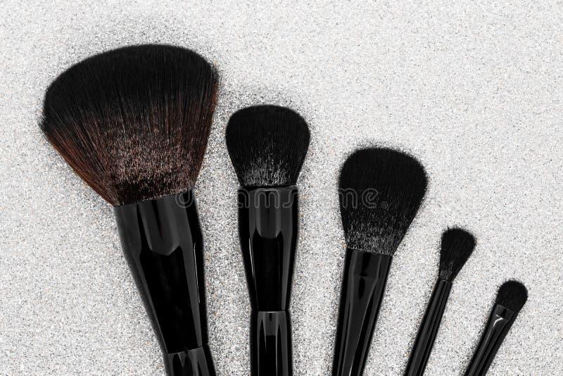 Czarni i brąz makeup muśnięcia na błyszczącym srebnym tle ukazują się obrazy stock