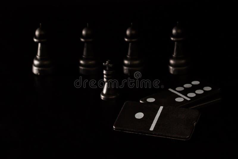 Czarni kostka do gry domina i szachowi kawałki na ciemnym tle obraz stock