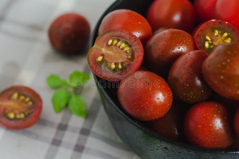 Czarni kumato pomidory w pucharze na stole obraz royalty free