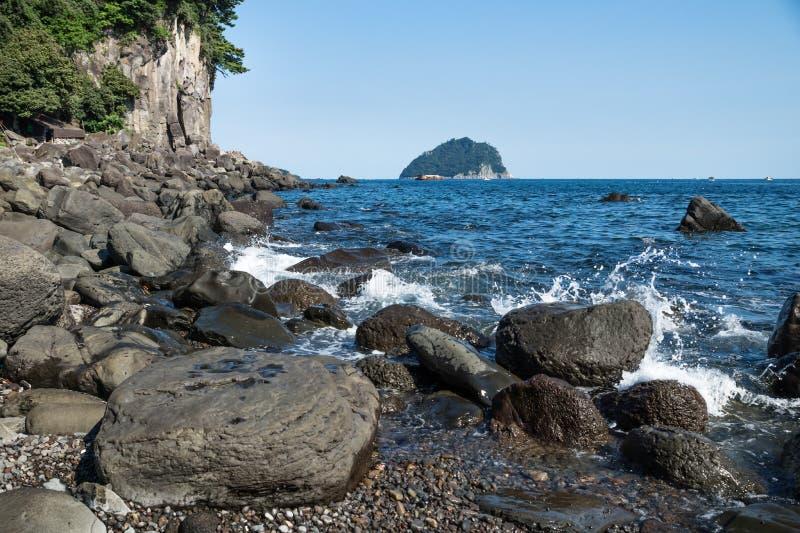 Czarni powulkaniczni kamienie z watersplash wzdłuż linii brzegowej Seogwipo, Jeju wyspa, Południowy Korea zdjęcie stock