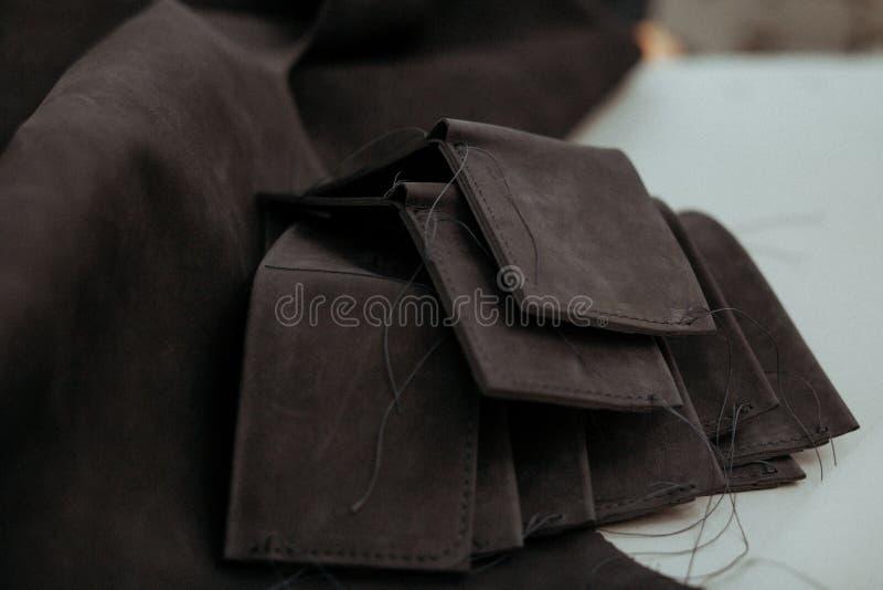 Czarni rzemienni kawałki czarna skóra na stole w warsztacie i portfle obrazy stock