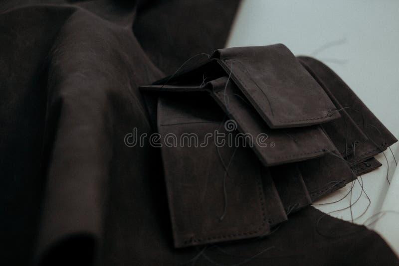 Czarni rzemienni kawałki czarna skóra na stole w warsztacie i portfle zdjęcia royalty free
