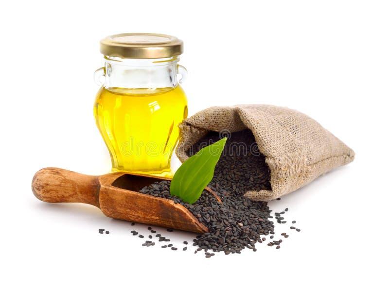 Czarni sezamowi ziarna z olejem pojedynczy białe tło obrazy stock
