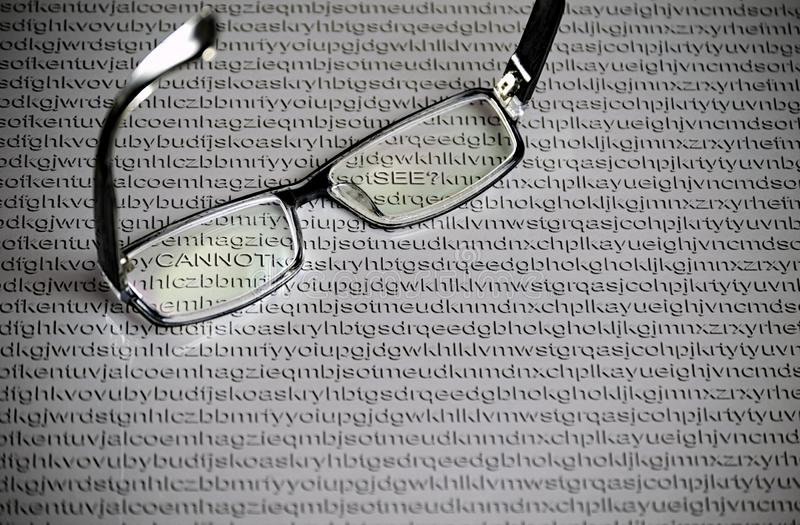 Czarni szkła na białej księgi tle z przypadkowymi listami Angielski abecadło, chujący słowa obraz stock