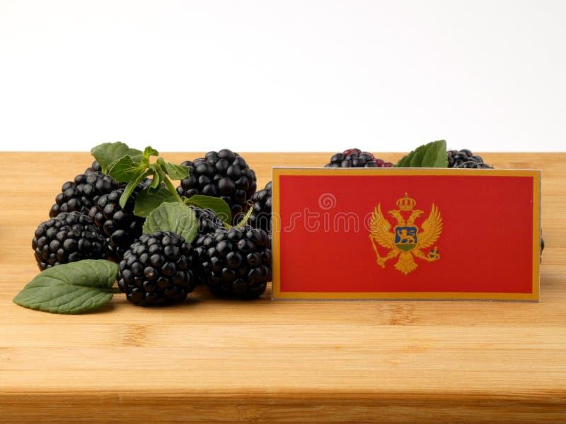 Czarnogórzec flaga na drewnianym panelu z czernicami odizolowywać dalej zdjęcia royalty free