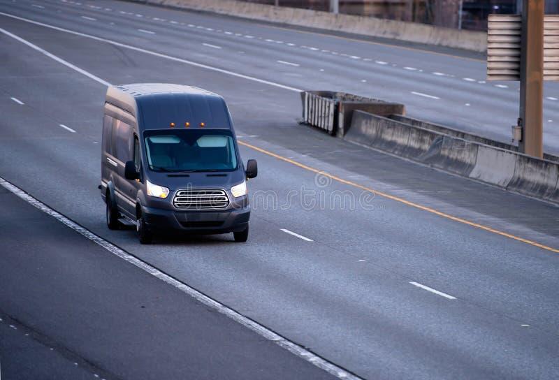 Czarny ładunek mini Samochód dostawczy Bieg na multiline drodze zdjęcia royalty free
