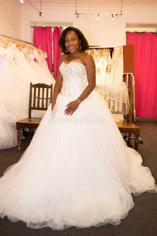 Czarny Afrykanin amerykańska kobieta próbuje małżeństwo suknię w sklepowej todze w ślubie fotografia royalty free