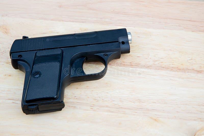 Czarny airsoft pistolet odizolowywający na drewnianym tle zdjęcie royalty free