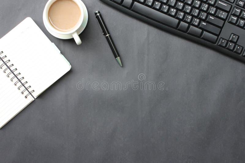 Czarny biurko z filiżanką, klawiaturą, notatnikiem i piórem umieszczającym wewnątrz, obrazy stock