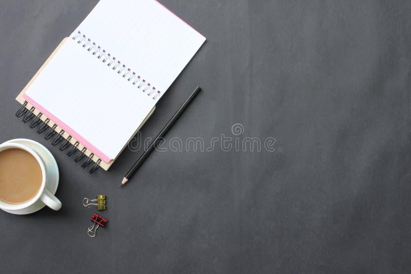 Czarny biurko z filiżanką, klawiaturą, notatnikiem i piórem umieszczającym wewnątrz, zdjęcie stock