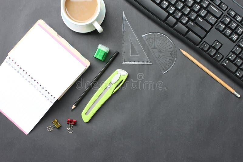 Czarny biurko z filiżanką, klawiaturą, notatnikiem i piórem umieszczającym wewnątrz, zdjęcia royalty free
