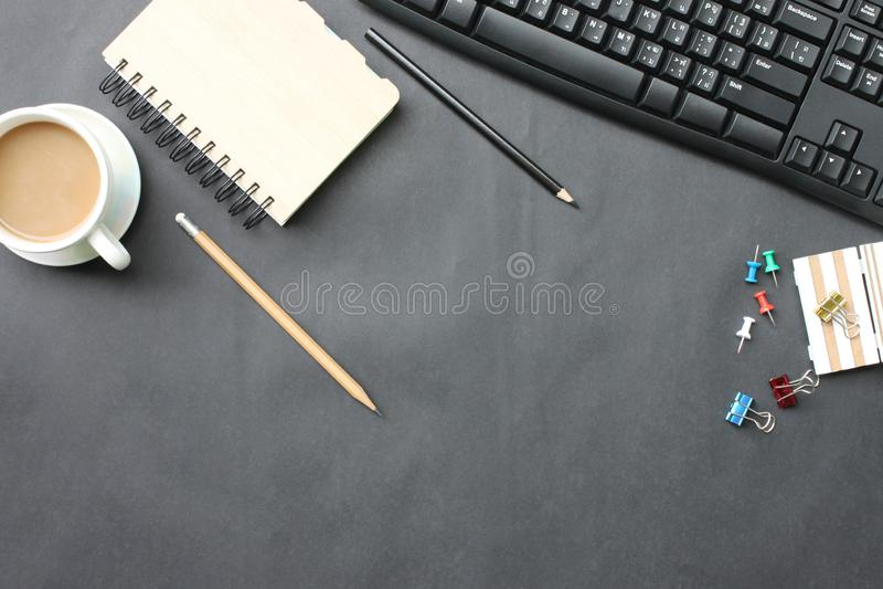 Czarny biurko z filiżanką, klawiaturą, notatnikiem i piórem umieszczającym wewnątrz, obraz stock