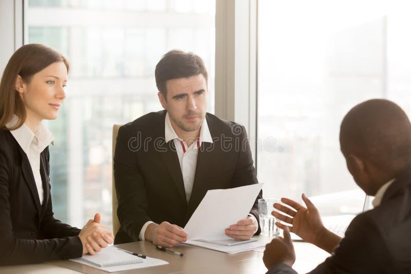 Czarny biznesmen przekonuje partnerów podpisywać dokument, negotiat zdjęcia stock