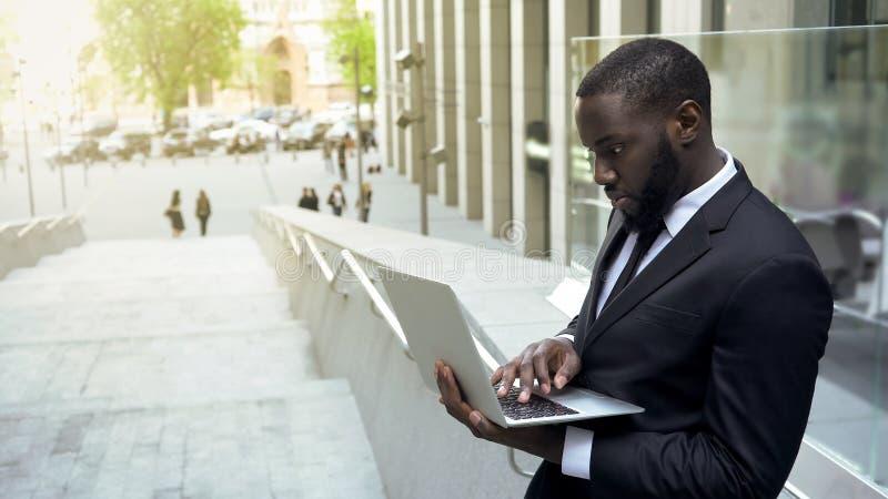 Czarny biznesmen sprawdza kartoteki na laptopie, przepracowywa się podczas przerwa na lunch zdjęcie royalty free