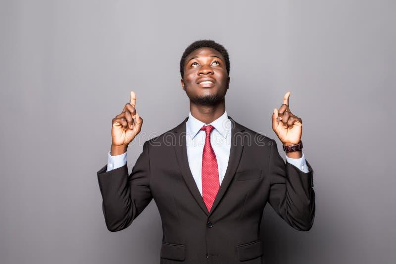 Czarny biznesowy mężczyzna wskazuje w górę odosobnionego nadmiernego bielu fotografia stock