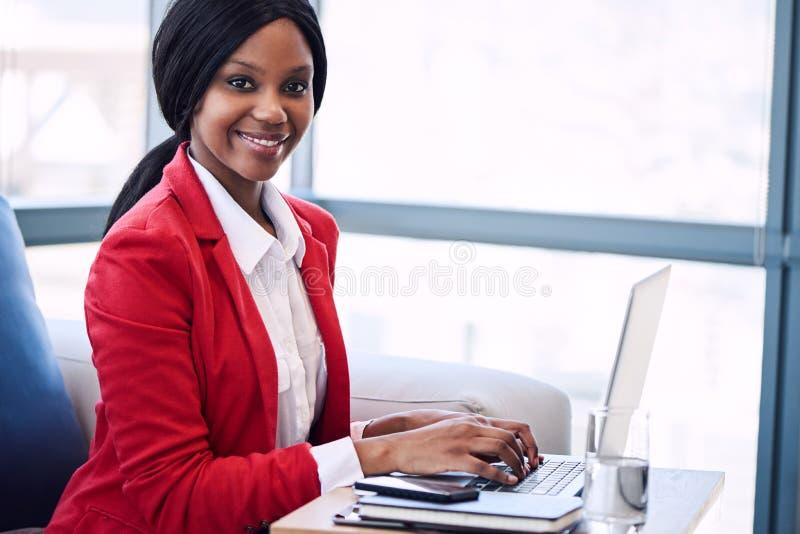 Czarny bizneswoman patrzeje w kamerę z jej rękami na laptopie fotografia stock