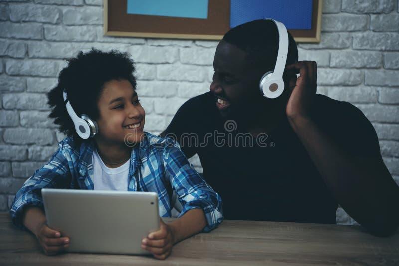 Czarny chłopiec nastolatek w hełmofonach i szczęśliwym ojcu zdjęcie stock