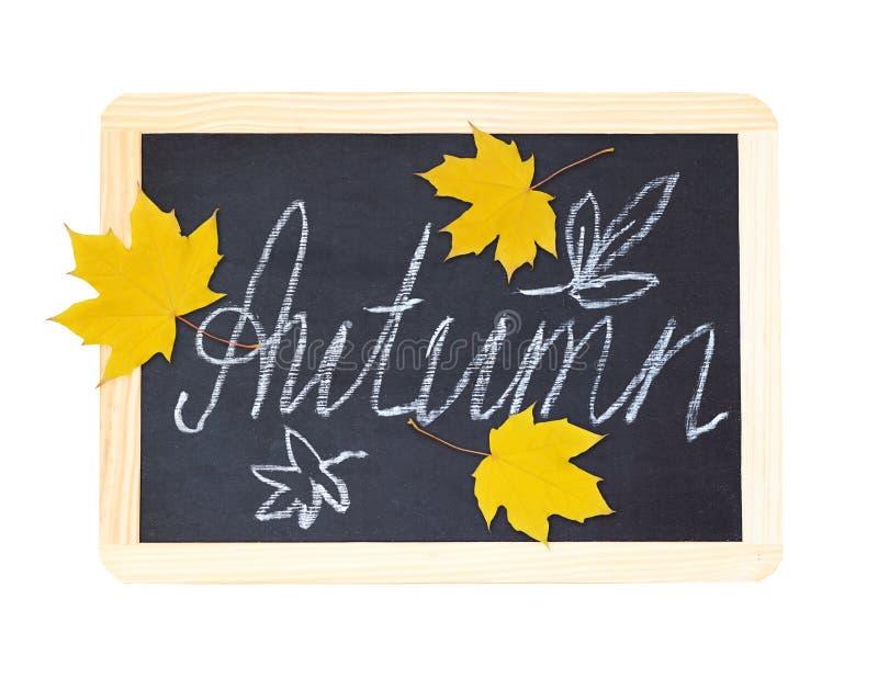 """Czarny chalkboard z ręcznie pisany kredowym literowaniem """"jesień"""" i żółci liście klonowi zdjęcie royalty free"""