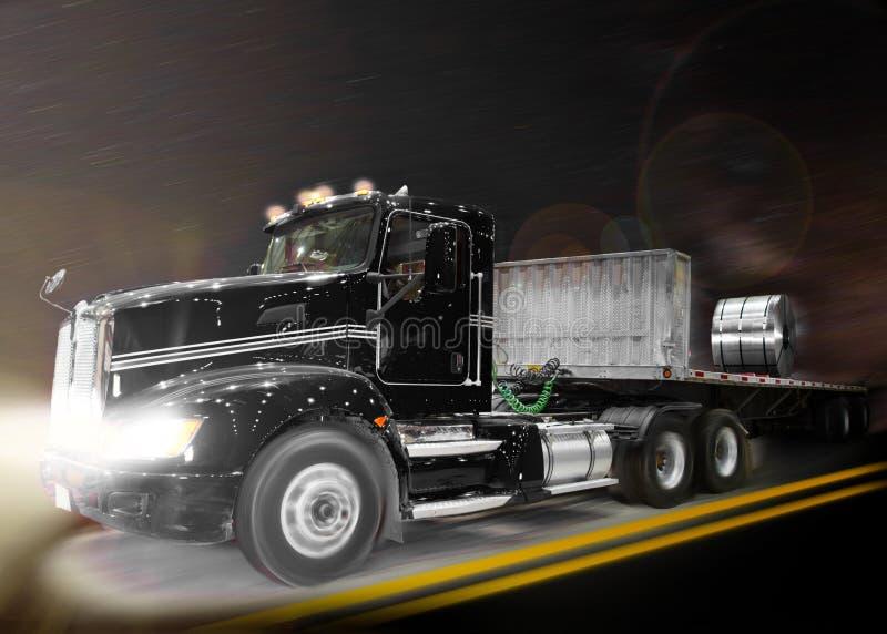 Czarny ciężarowy popędzać przez elementów przy nocą fotografia stock