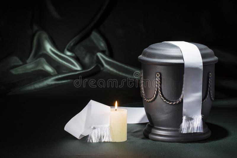 Czarny cmentarniany łzawica z płonącej świeczki białym faborkiem na głębokim, - zielony tło fotografia royalty free