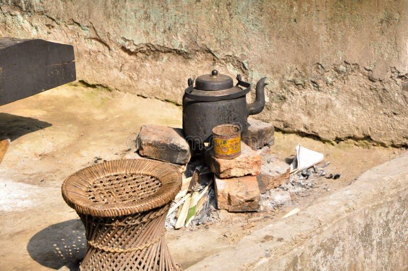 Czarny czajnik na cegłach gotować się wodę i robić herbaty w wiosce w ranku dla domowego chwyta używa z Tradycyjnym indyjskim sie obraz royalty free