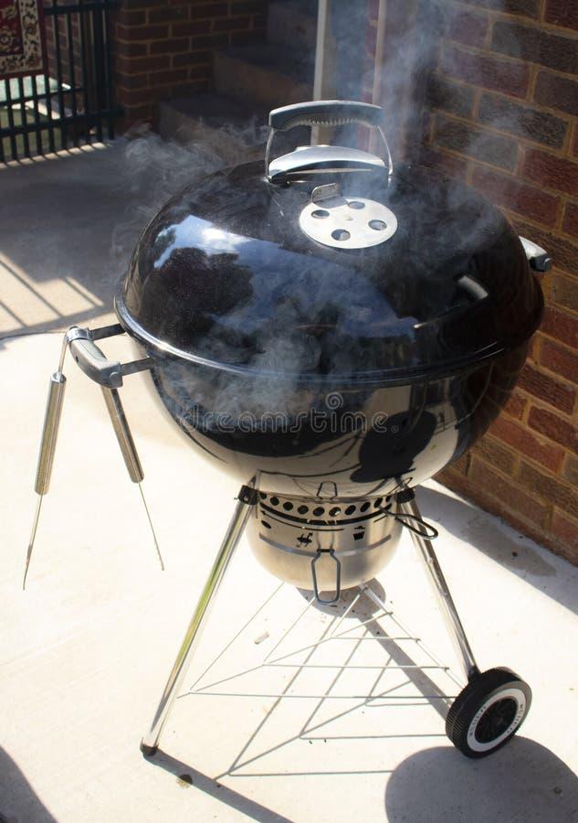Czarny czajnika typ plenerowy węgla drzewnego grilla obsiadanie na patiu obok ściana z cegieł z dymnym przybyciem z go i para na  zdjęcie royalty free