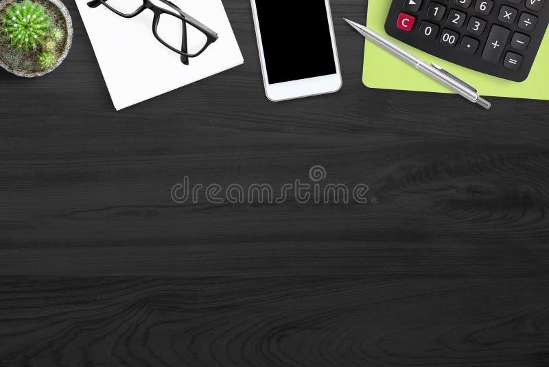 Czarny drewniany biurowego biurka stół z kalkulatorem i dostawami, biznesowy pojęcie Odg?rny widok z kopii przestrzeni?, mieszkan zdjęcia stock