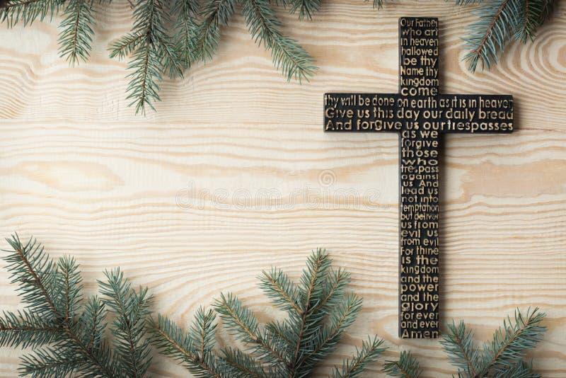 Czarny drewniany krzyż z władyki modlitwą na podławej drewnianej desce z jedlinowym gałąź tłem obrazy stock
