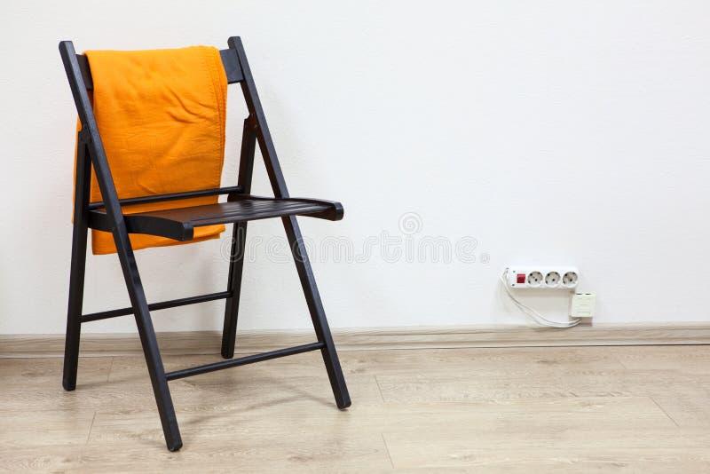 Czarny drewniany przypala trwanie pobliską ścianę z pomarańczową szkocką kratą zdjęcie stock