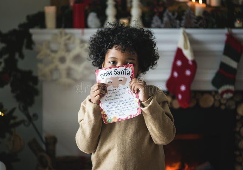 Czarny dzieciak z Bożenarodzeniowym wishlist papierem fotografia royalty free