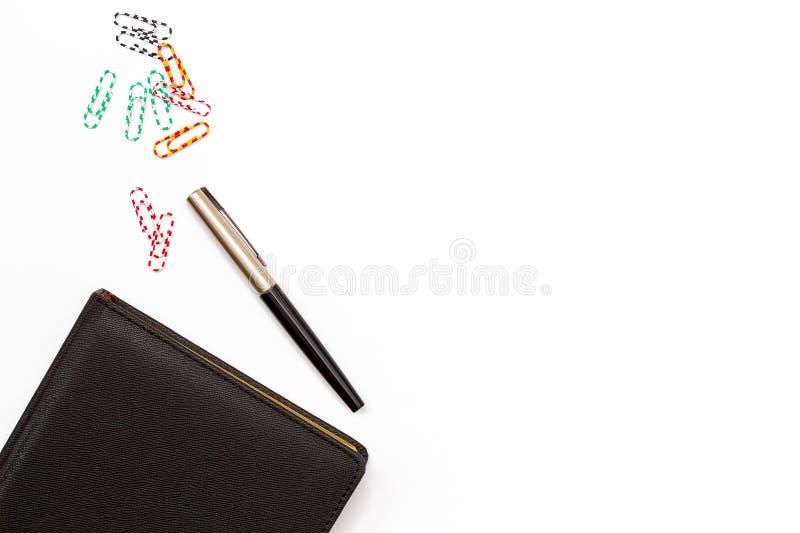 Czarny dzienniczek, pióro i barwioni paperclips na białym tle, Biurko w biurze minimalny biznesowy pojęcie Mieszkanie nieatutowy fotografia royalty free
