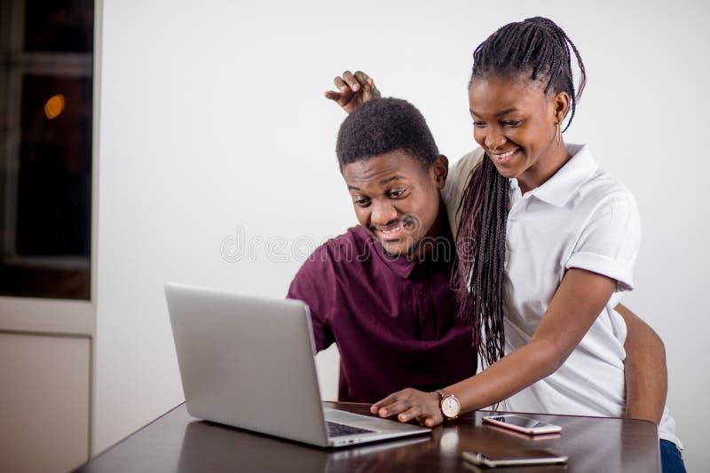 Czarny dziewczyny obsiadanie przed laptopem s patrzeje na ekranie obrazy royalty free