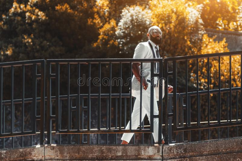 Czarny elegancki mężczyzna przechodzi most obraz royalty free