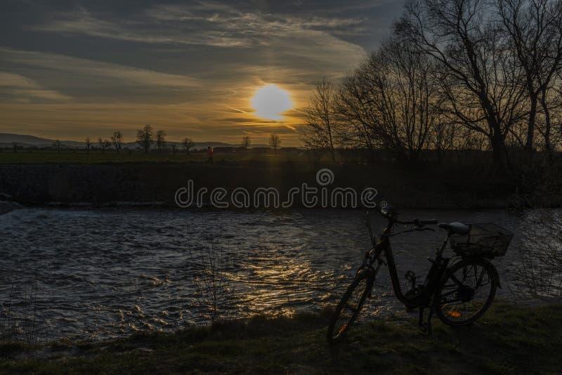 Czarny elektryczny bicykl z zmierzchem blisko jazu na Malse rzece zdjęcia stock