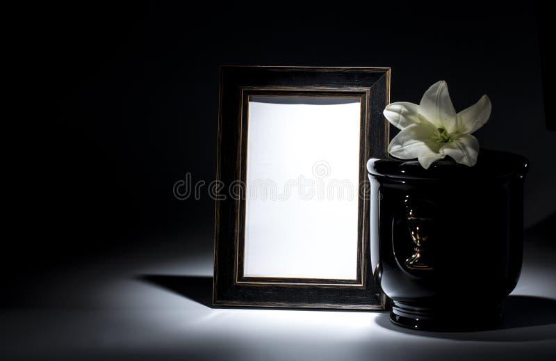 Czarny ewangelicki łzawica z pustą opłakuje ramą i kwiatem, zdjęcia royalty free